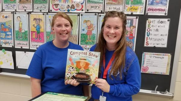"Two Green Iowa members with the book, ""Compost Stew"""