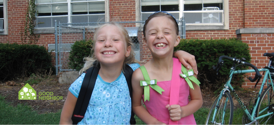 Two girls smiling in front of school